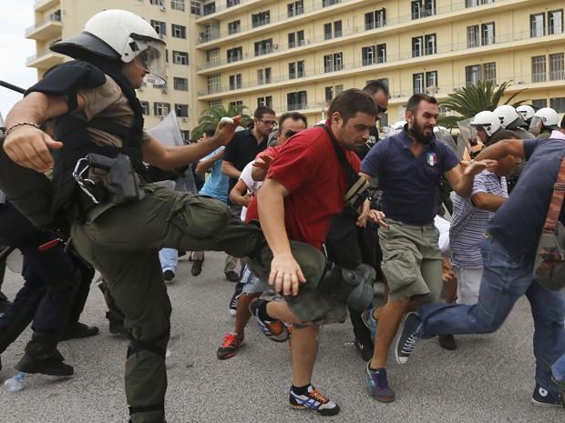 Policial chuta manifestantes que tentam escapar de ser detidos durante manifestação no pátio do Ministério da Defesa em Atenas, nesta quinta-feira (4). A polícia grega e trabalhadores de estaleiros entraram em confronto.  (Foto: Reuters)